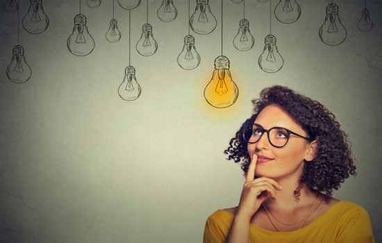 Woman thinking with light bulbs in background