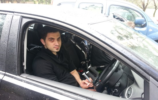Man sitting in car with assistive steering wheel