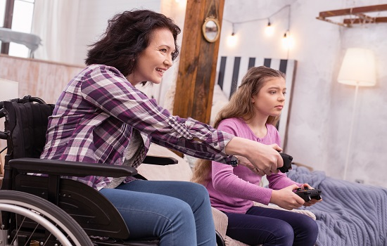 Woman in wheelchair and daughter playing video game