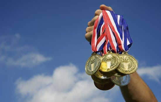 Inform paralymians. Image is of someone holding up a bunch of sports medals against a blue sky backdrop.