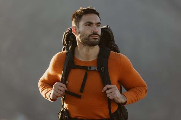 Man hiking wearing orange icebreaker merino oasis base layer thermal top