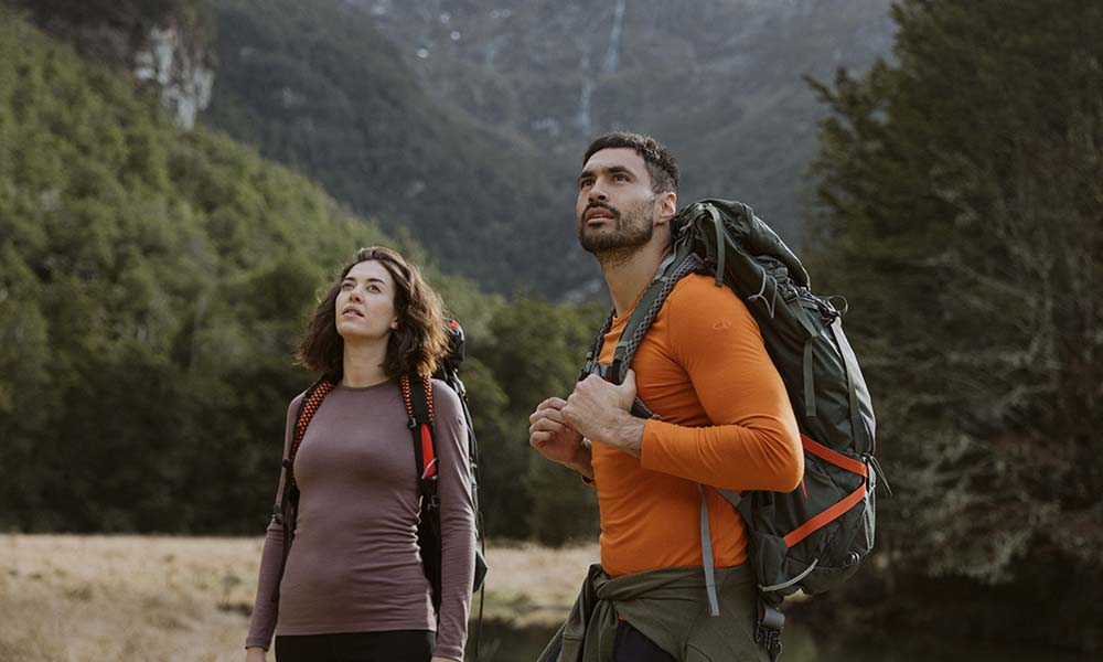 Man and woman hiking wearing icebreaker merino oasis base layer thermal tops