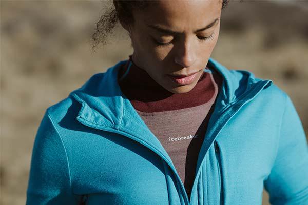 Woman standing on rocks wearing blue icebreaker merino Quantum III hoodie