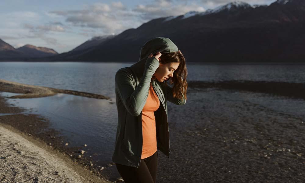 Woman standing near a lake wearing a green icebreaker merino Quantum III hoodie