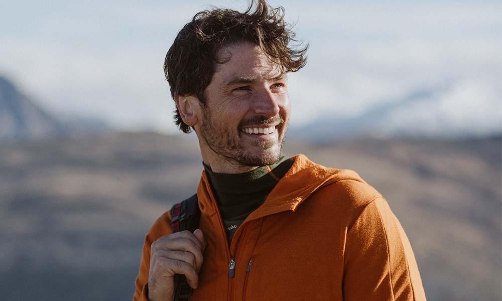 Man hiking wearing an orange icebreaker merino Quantum III hoodie