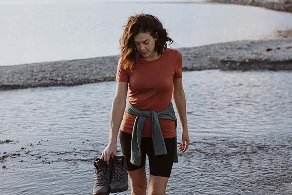 Woman wading through water wearing red icebreaker merino Tech Lite II t-shirt