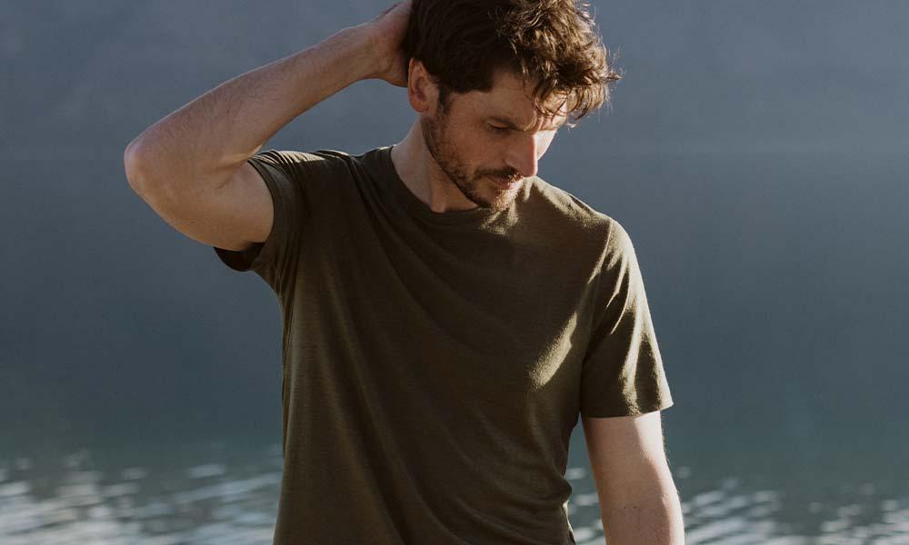 Man standing in front of lake wearing green icebreaker merino Tech Lite II t-shirt