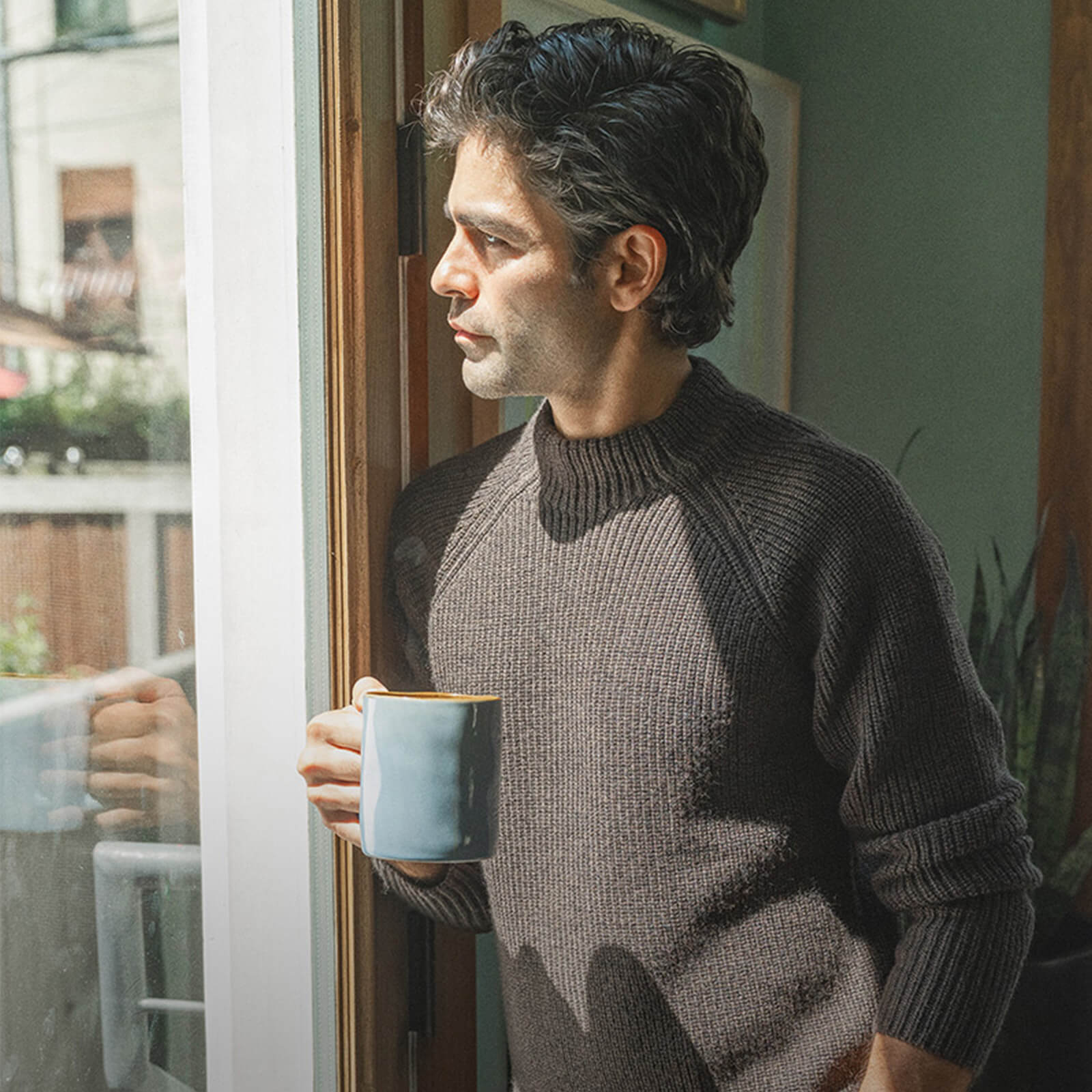 Adrian Grenier by a window having a drink in a cup