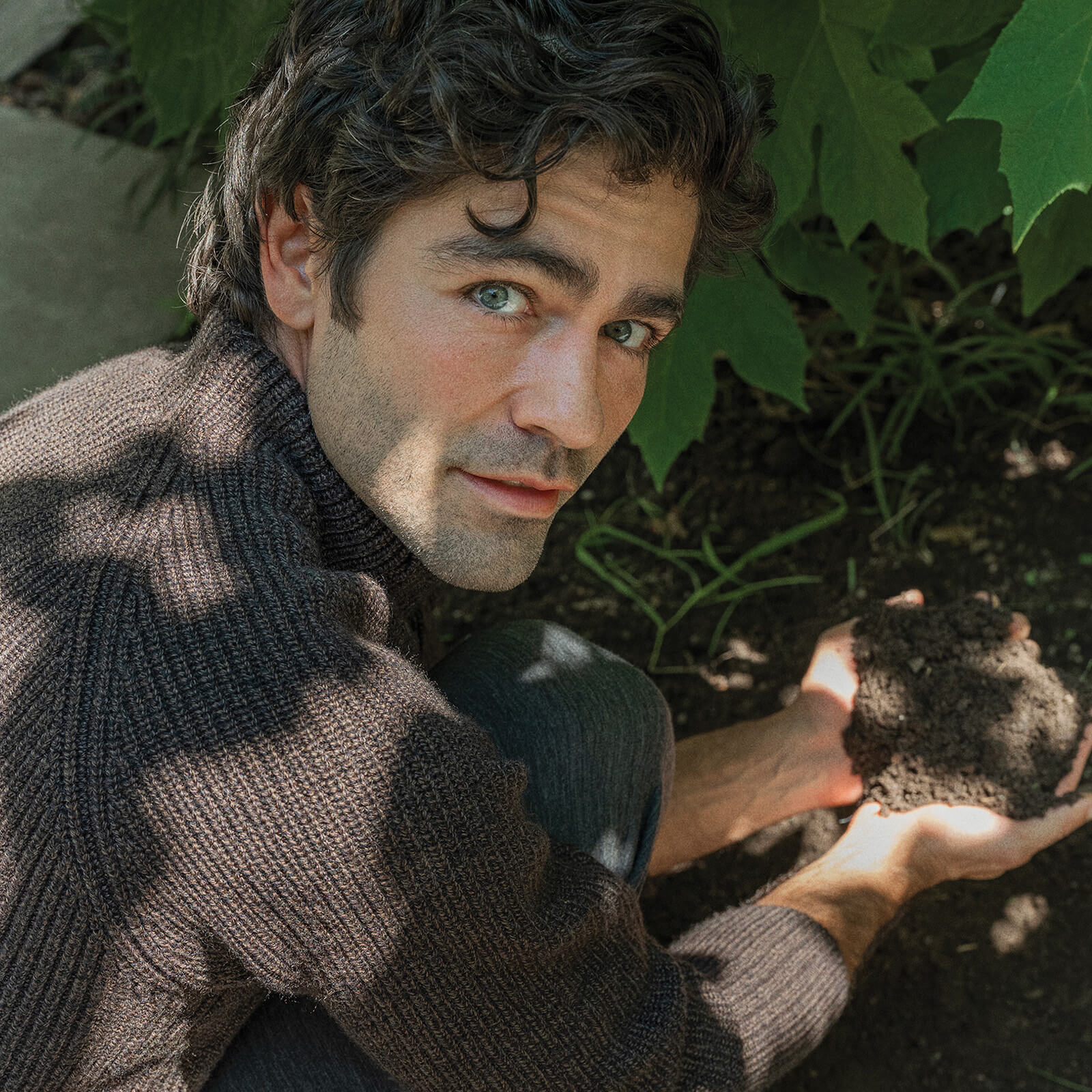 Adrian Grenier wearing icebreaker touching soil in his garden