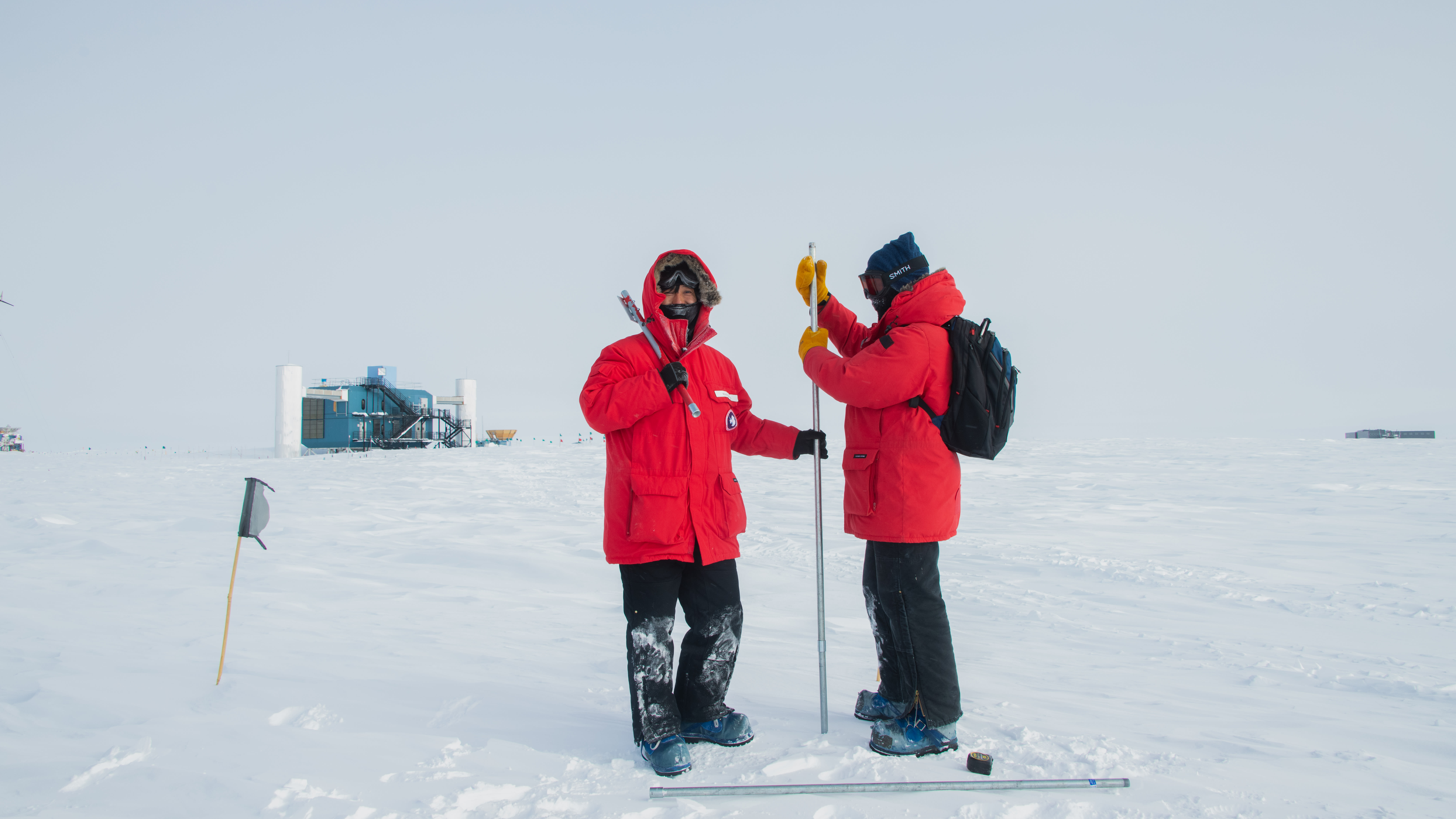 A couple of IceCube scientists at the South Pole taking snow measurements. The IceCube Laboratory is in the background on the left.