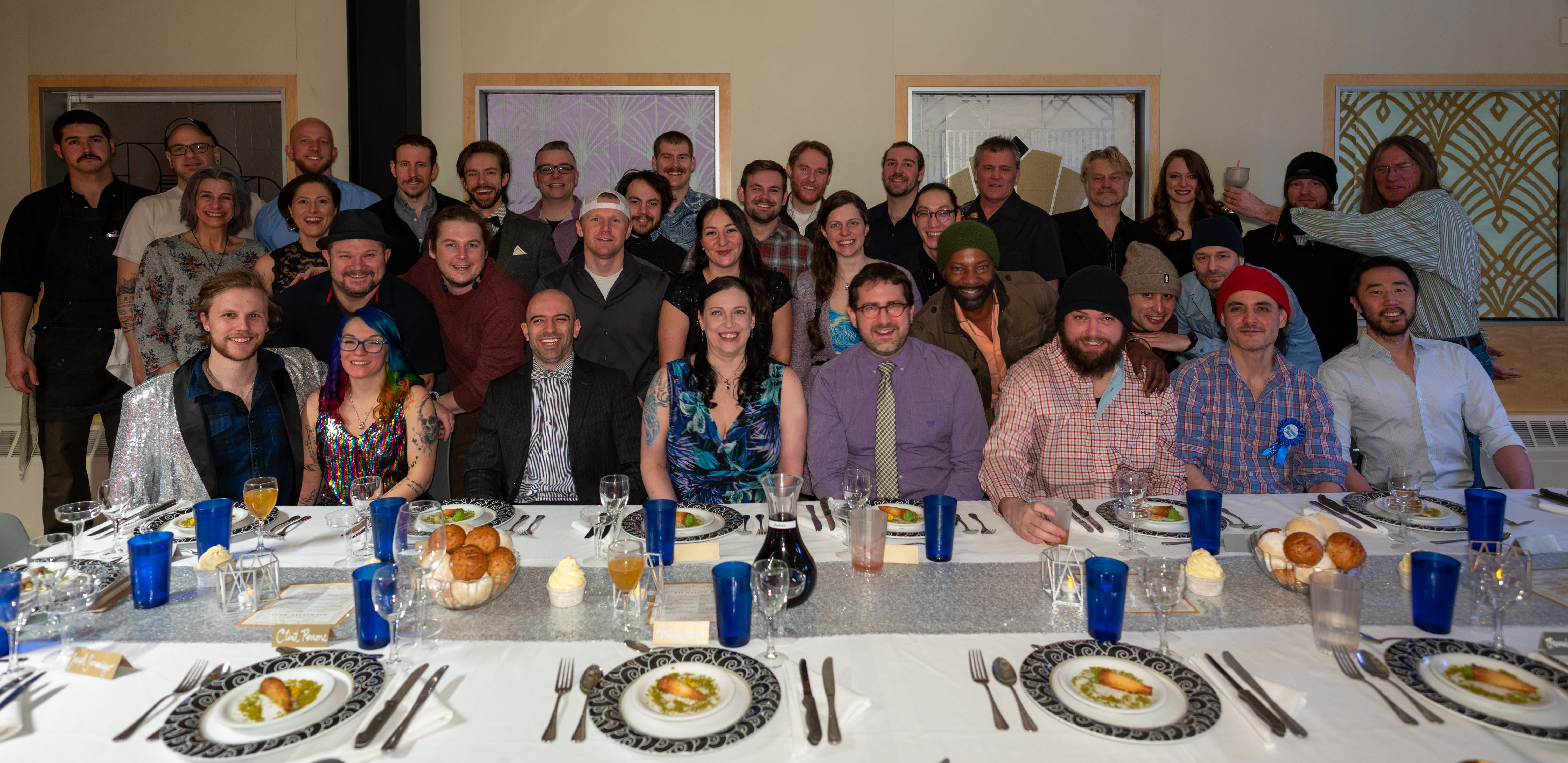 Group photo, seated at long table for midwinter meal.