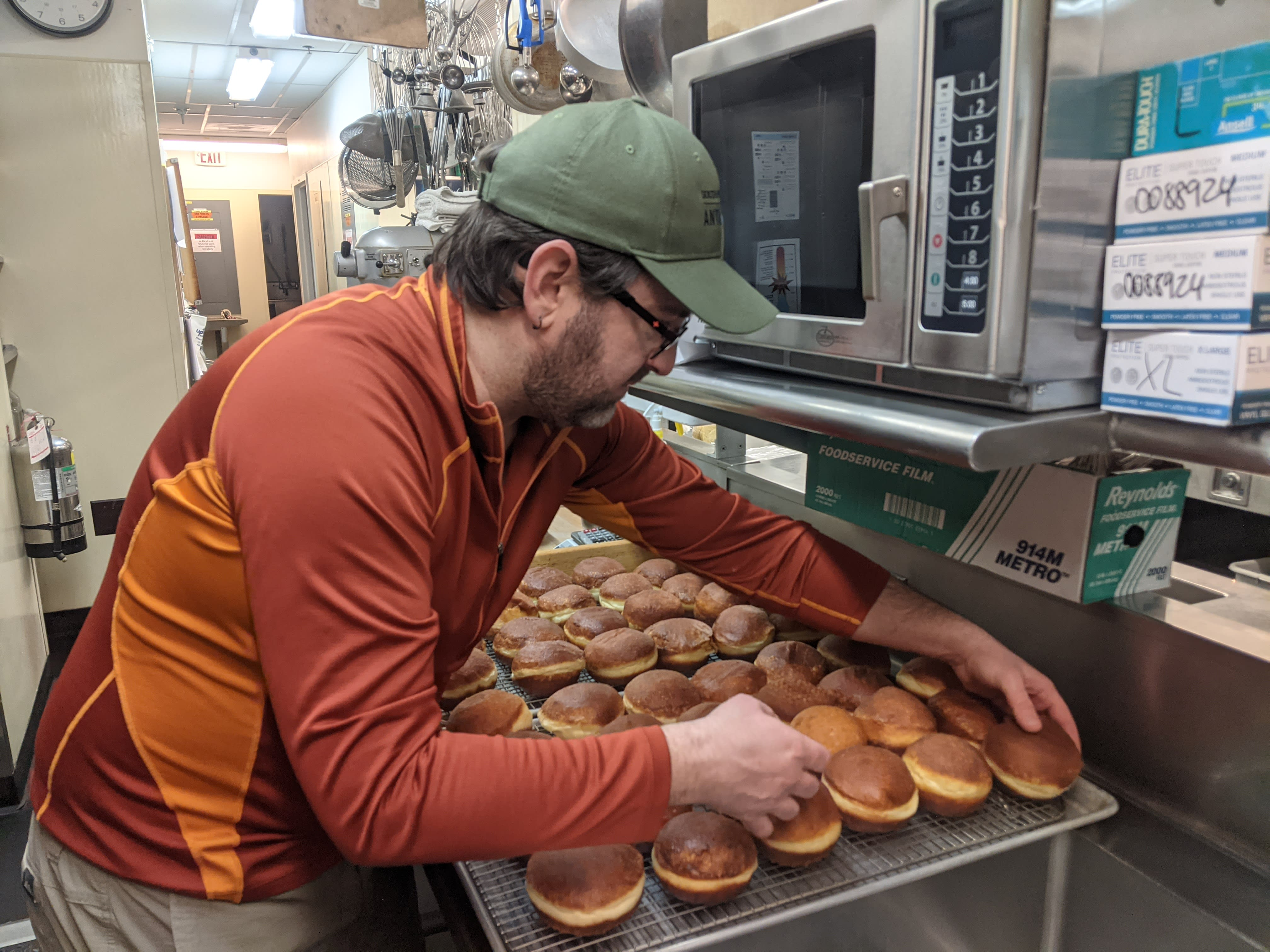 Person arranging donuts on a cooling rack.