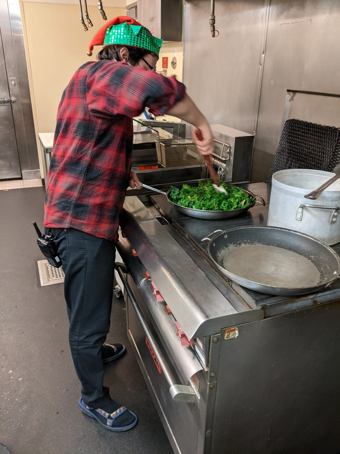 Person seen from side, standing at industrial stove and stirring a pan of greens.
