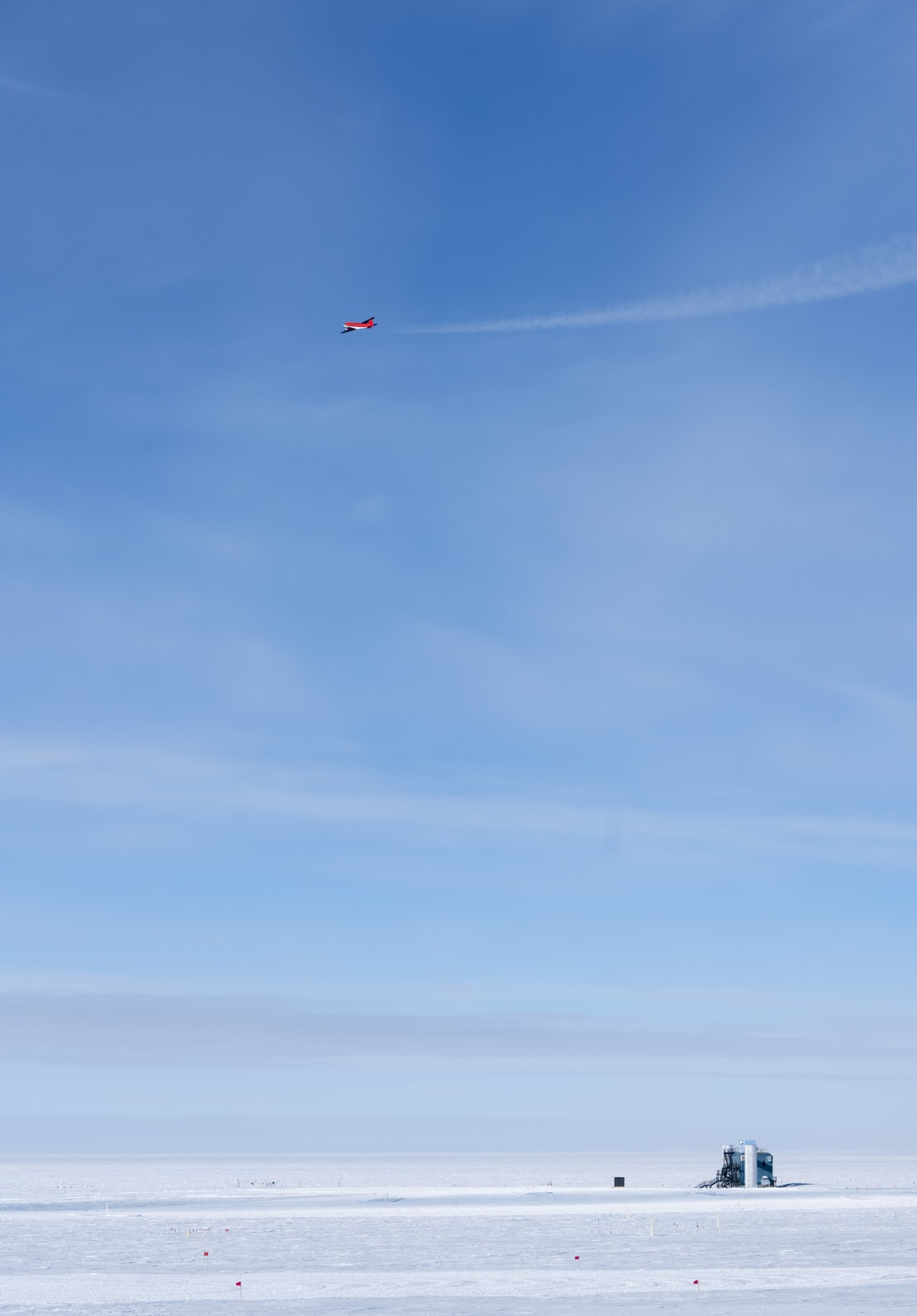 A plane with contrails high in a blue sky over the IceCube Lab, appearing small in lower right.