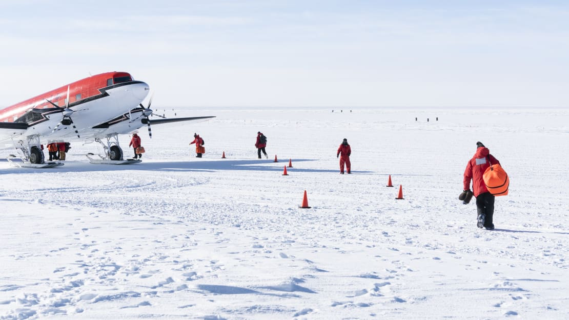 Several people in red parkas from behind making their way toward a plane waiting on the ice.