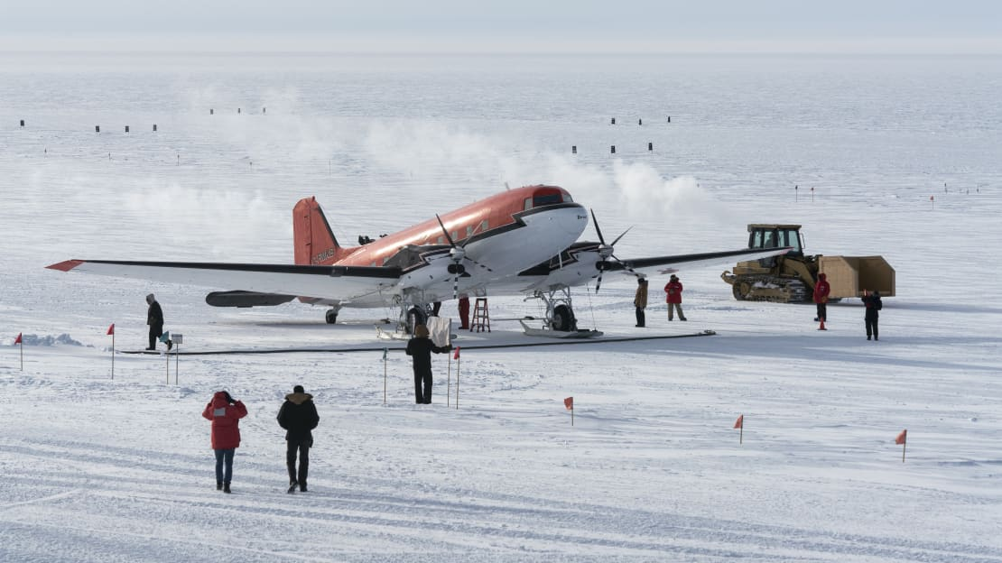 Arriving winter personnel walking away from plane parked on the skiway at South Pole.