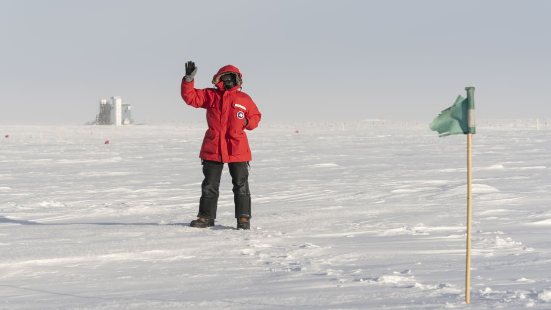 Person in red parka waving, with the IceCube Lab in the distance.