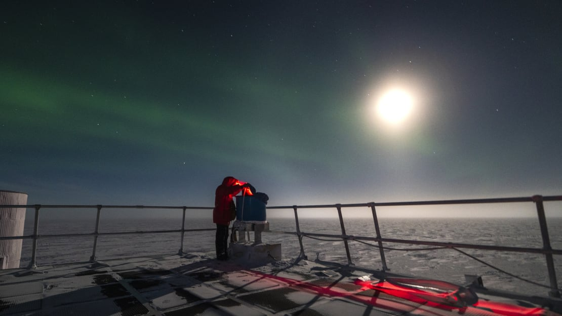 Person outdoors working on IceAct telescope, wearing red headlamp and lit from above by bright moon.