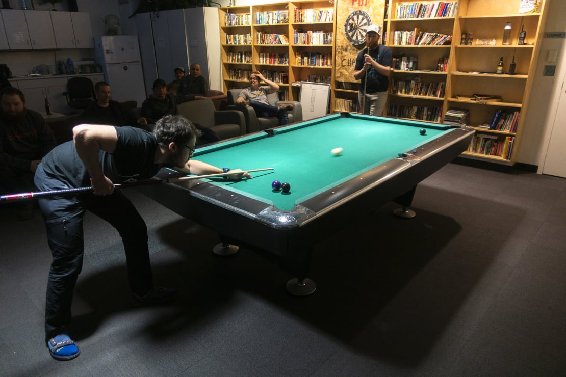Person bent over pool table in middle of a shot.