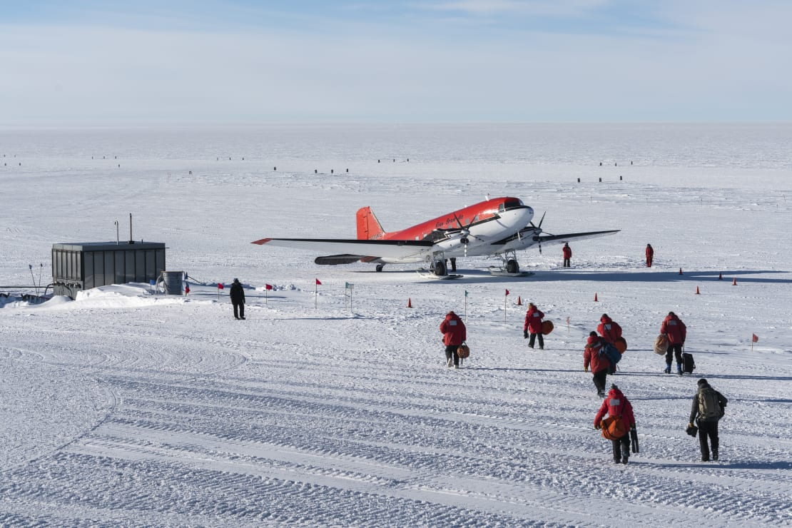 Departing summer personnel walking out to awaiting plane on the skiway at South Pole.