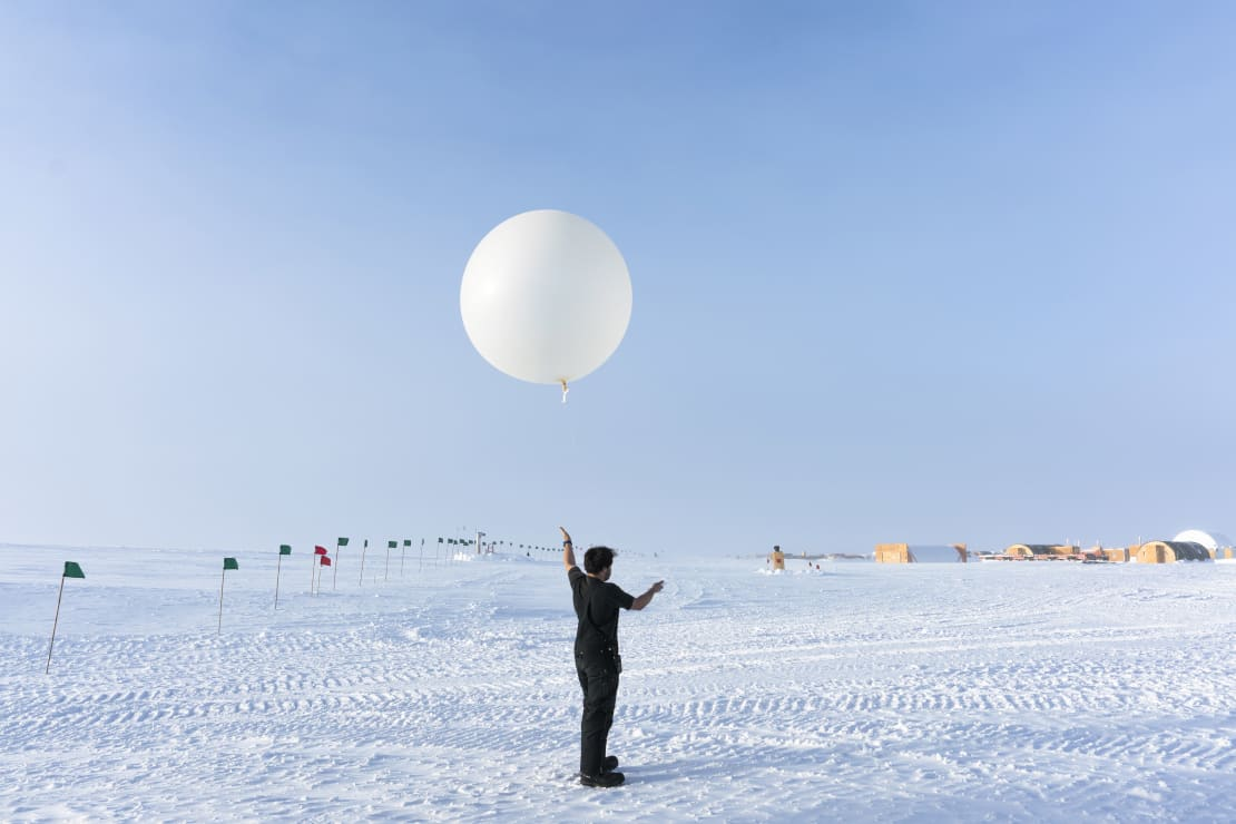 Winterover holding onto a weather balloon before launch.
