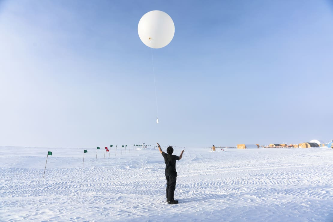 Winterover having just let go to launch a weather balloon.