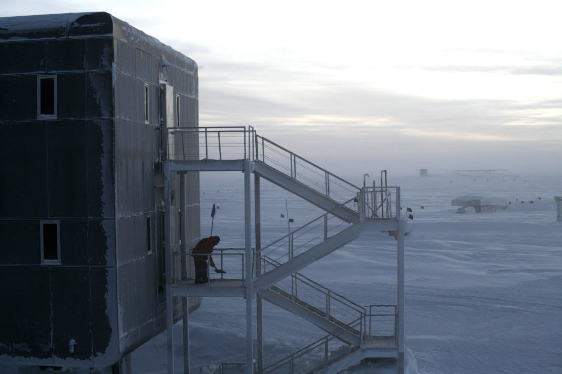 Person shoveling snow away from emergency exits outside the South Pole station.