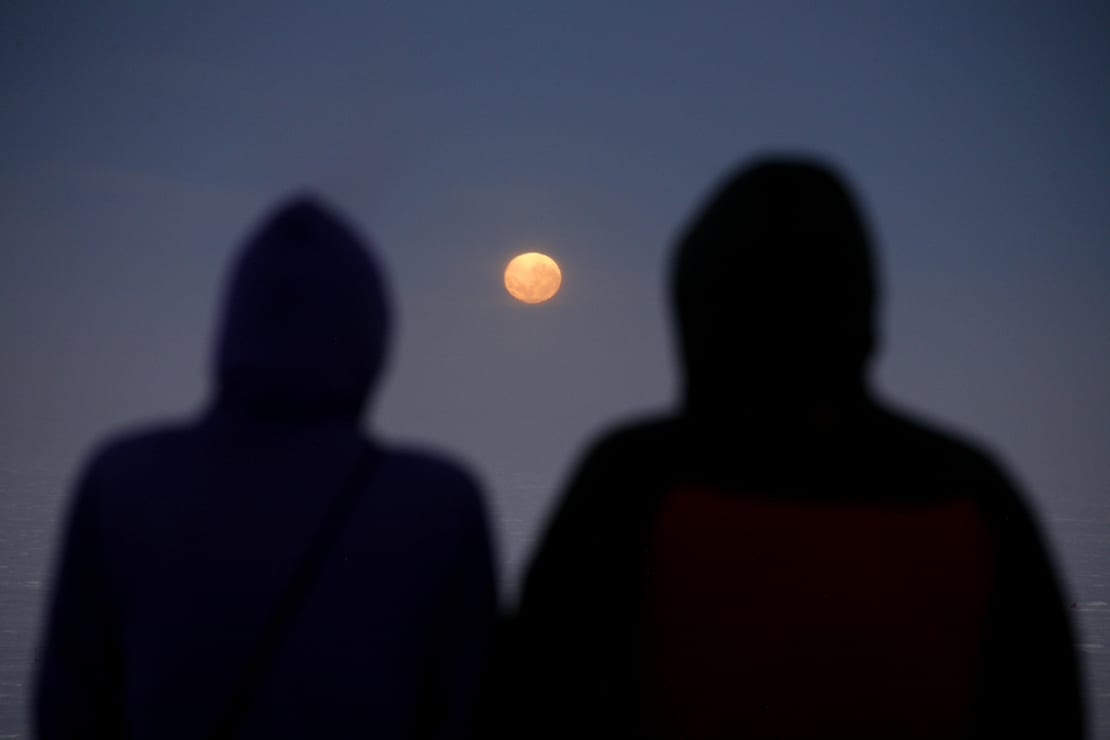 Blurry images of shadowed behinds of two hooded individuals facing a full moon, shown between them.