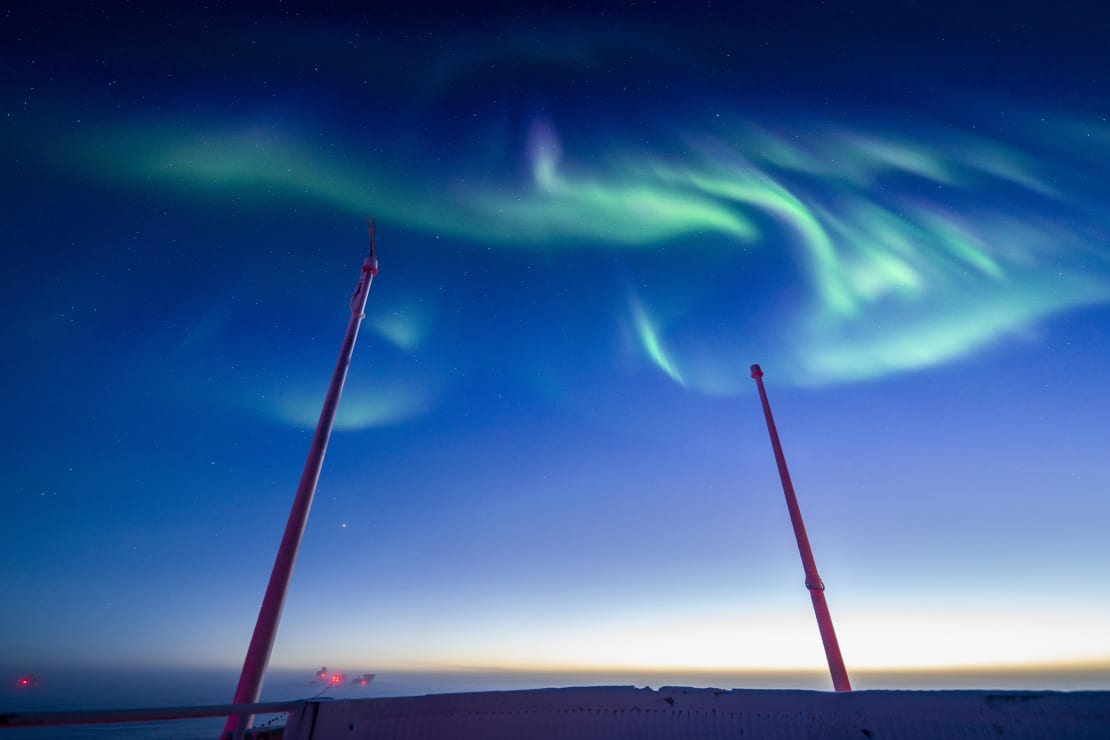 Swirling green auroras against blue sky, from observation deck of South Pole station.
