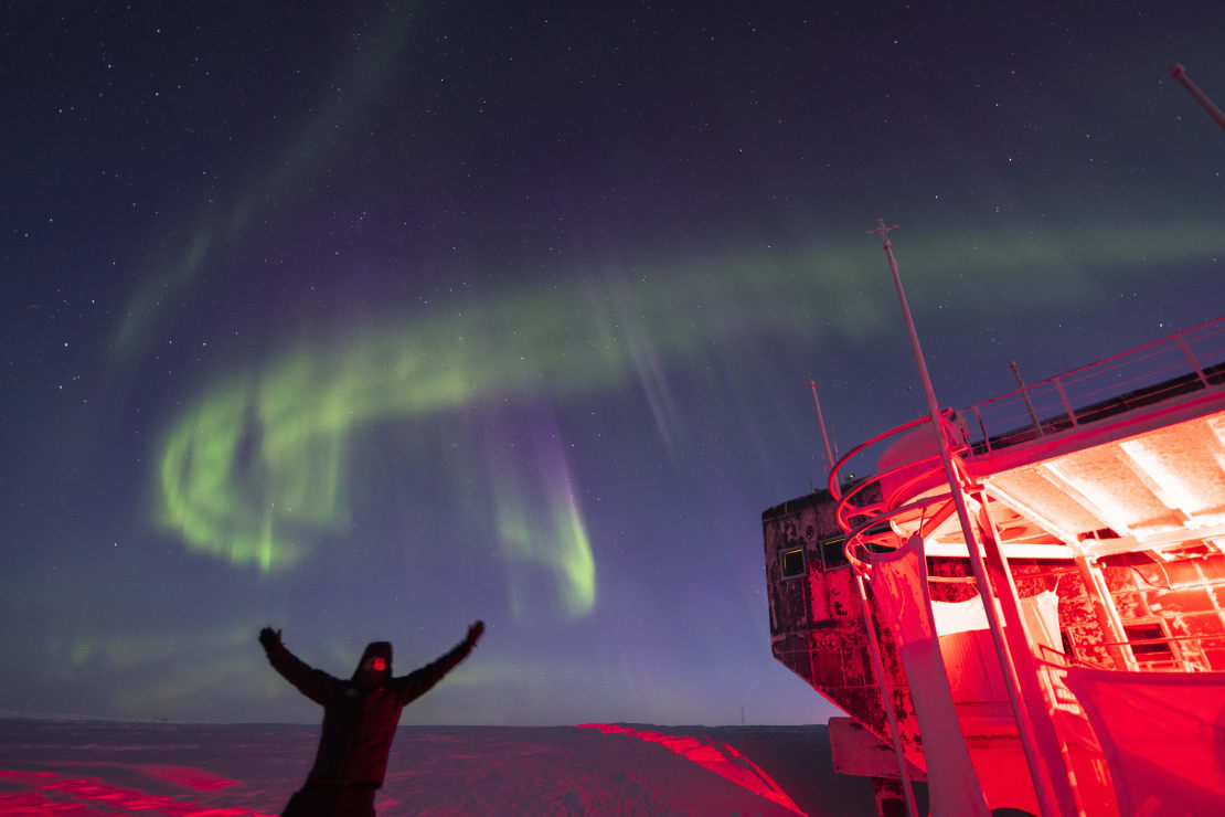 Person with arms thrown up into the air, with swirling aurora just overhead.
