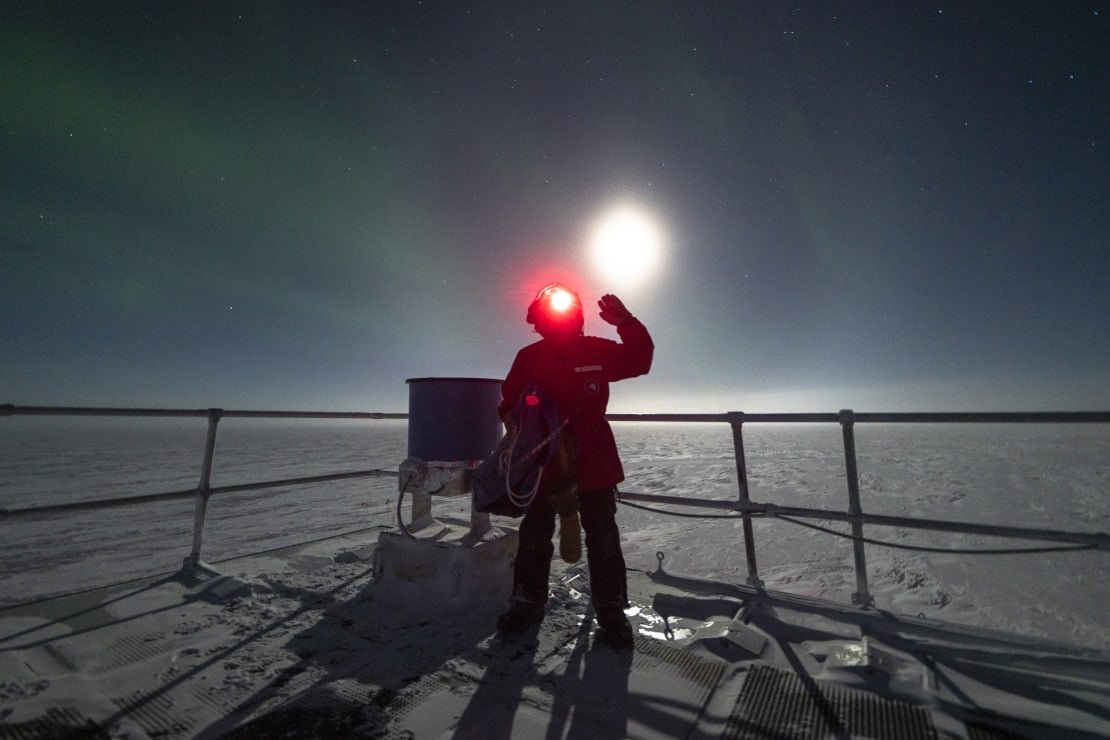Person wearing red headlamp facing camera and waving, standing next to IceAct telescope, with bright moon just above their head.