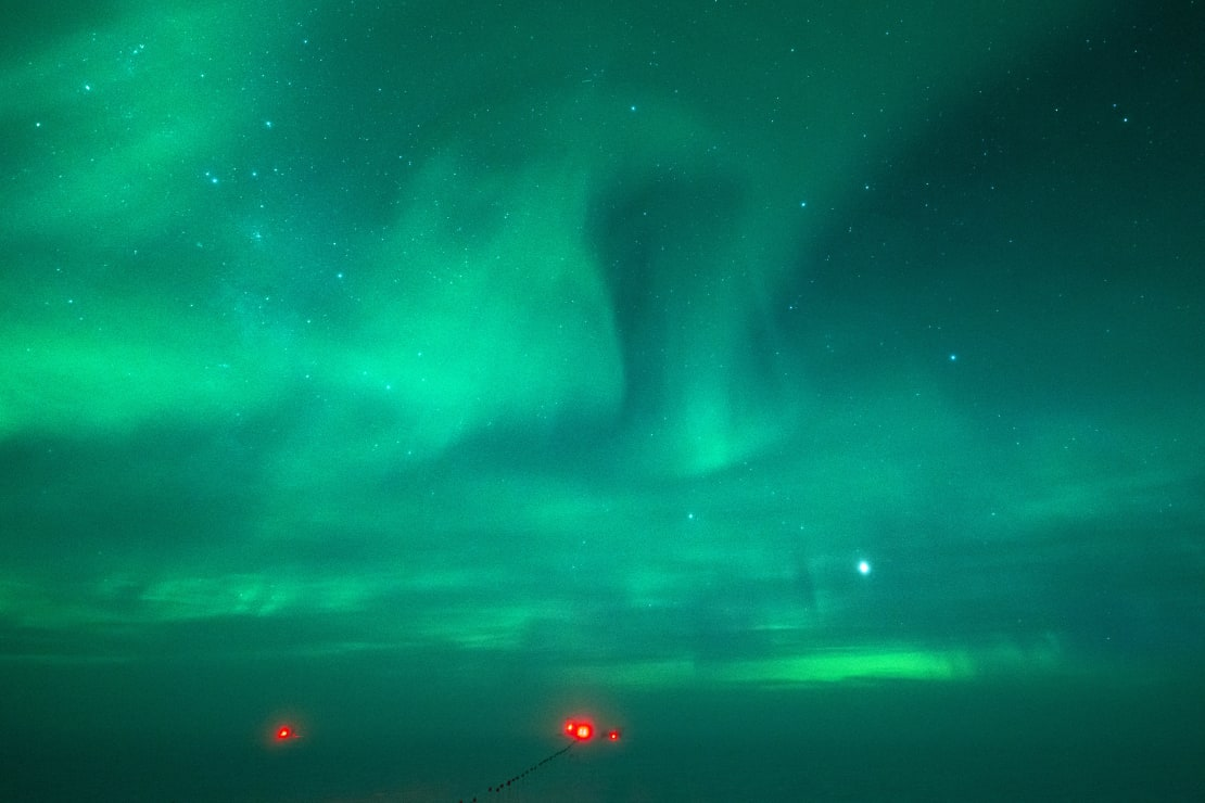 Sky and surface all bathed in green light from auroras.