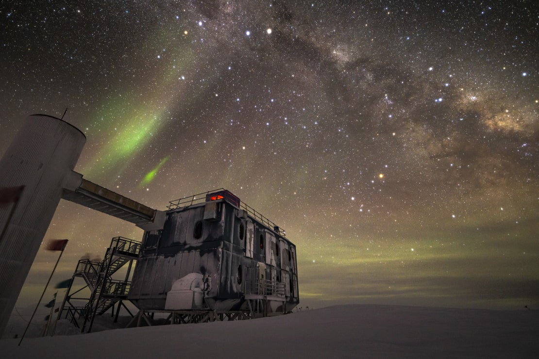 The backside of the IceCube Lab under a starry and aurora-filled sky.