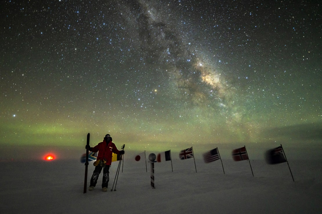 Winteover standing with ski poles at the ceremonial Pole with Milky Way overhead.