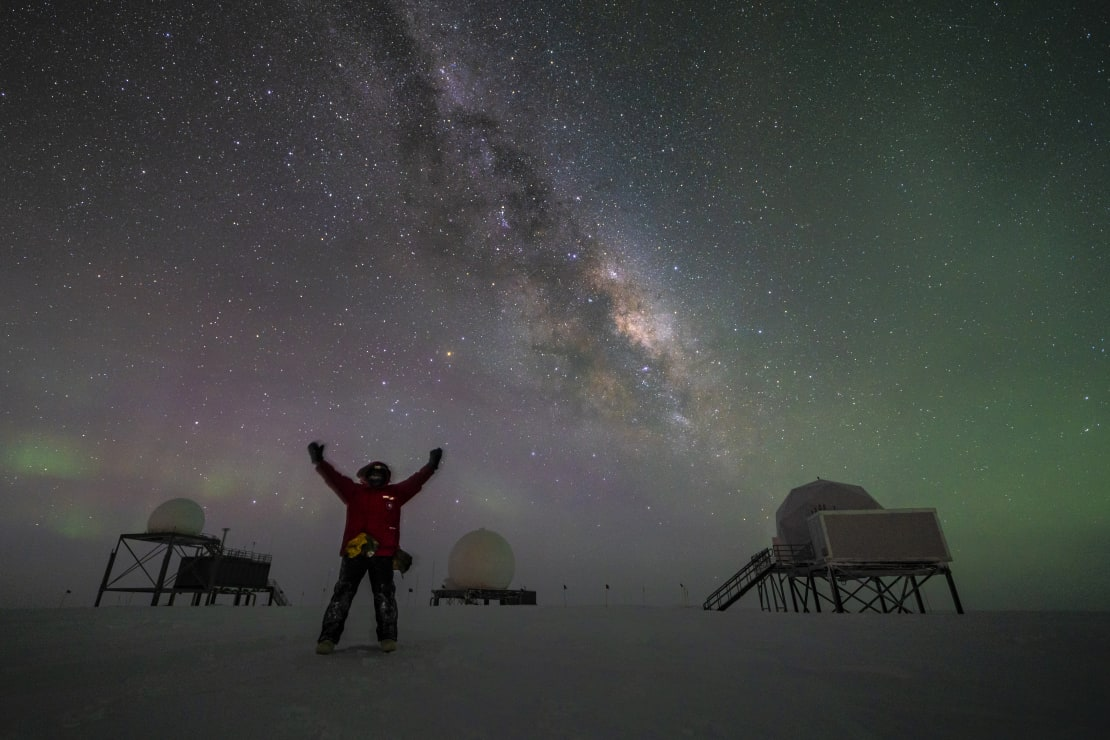 Person standing with arms up, and with three satellite dome structures in the background, and Milky Way, stars, and auroras in the sky.