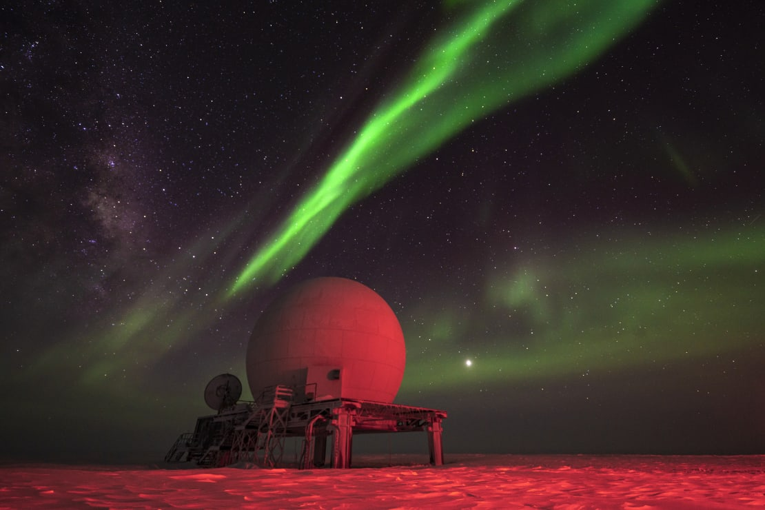 Satellite dome lit in red light, with streak of bright green aurora overhead.