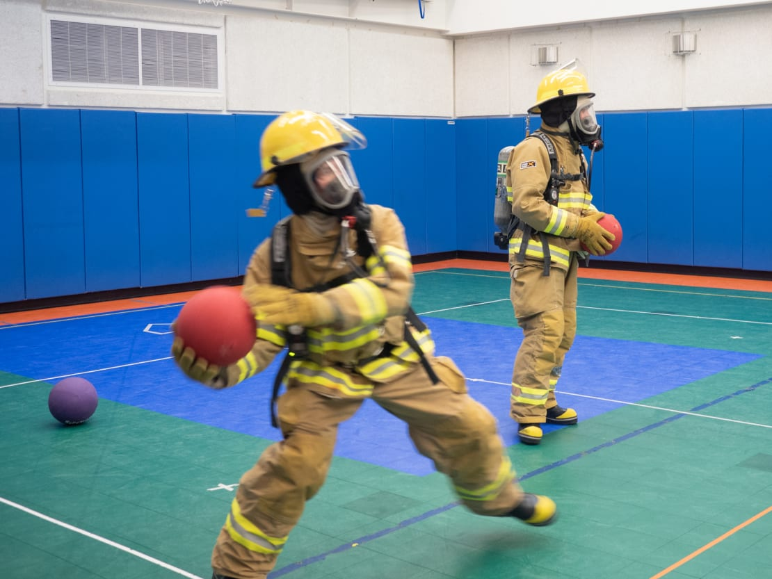 Two people in fire gear playing dodgeball in gym.]