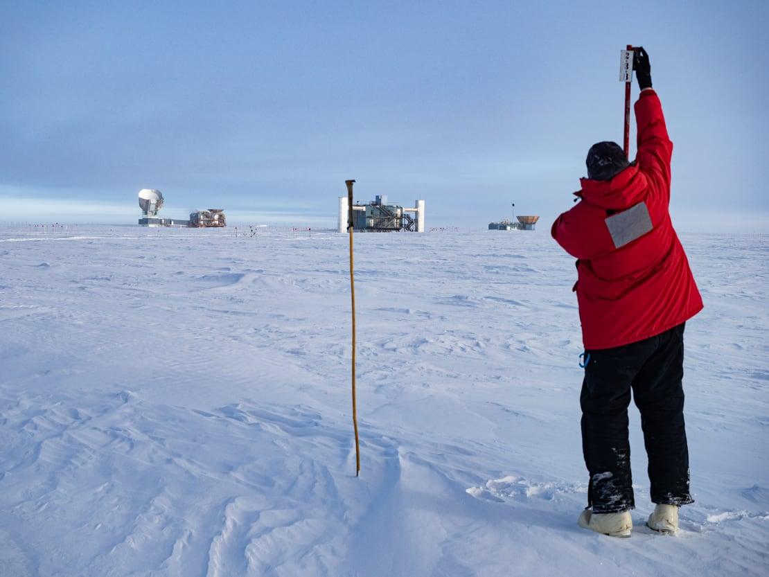 Winterover holding up measuring device, with IceCube Lab in background.