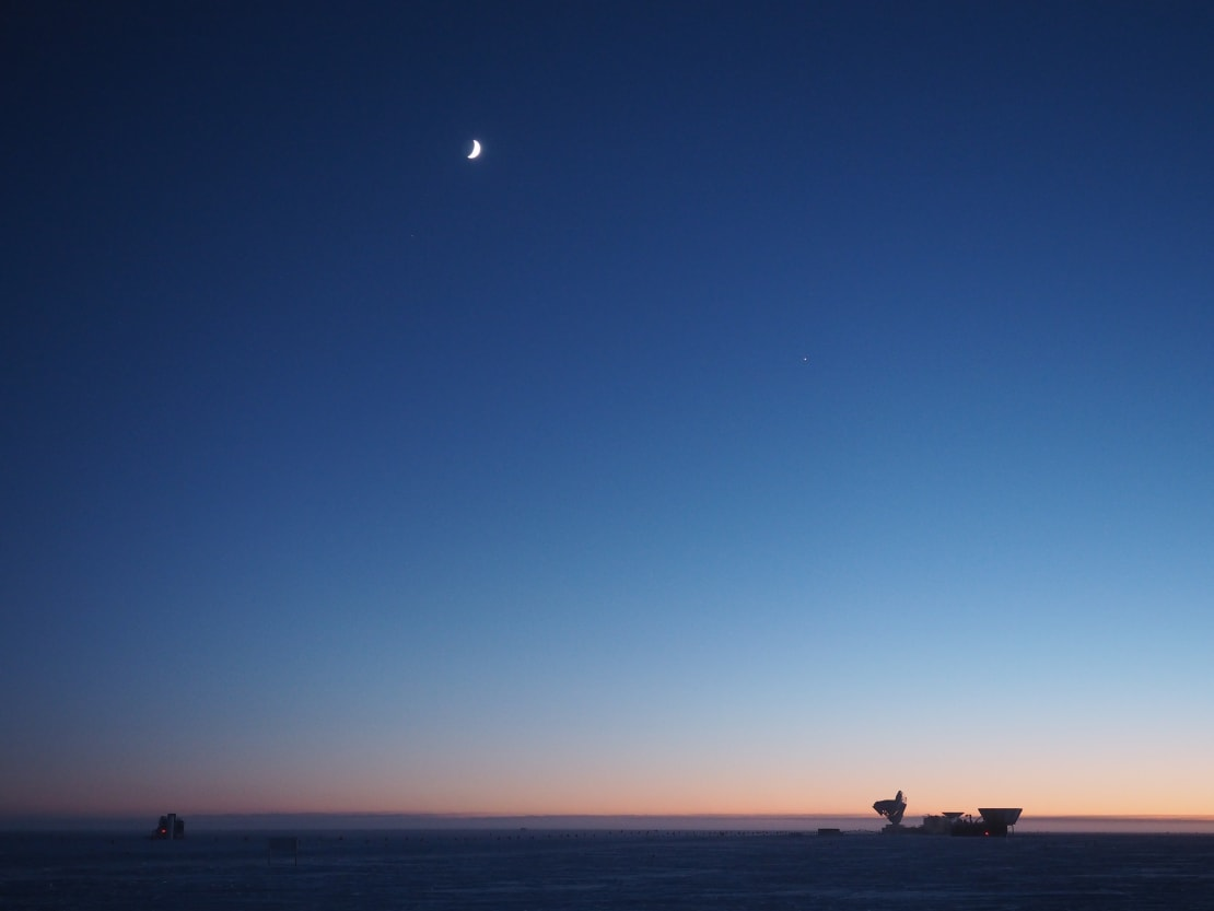Twilight at the South Pole, with crescent moon high in sky and orange hues along horizon.