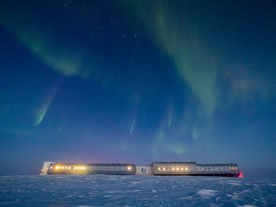 South Pole station on horizon, with light showing in some of the windows, and light auroras overhead.