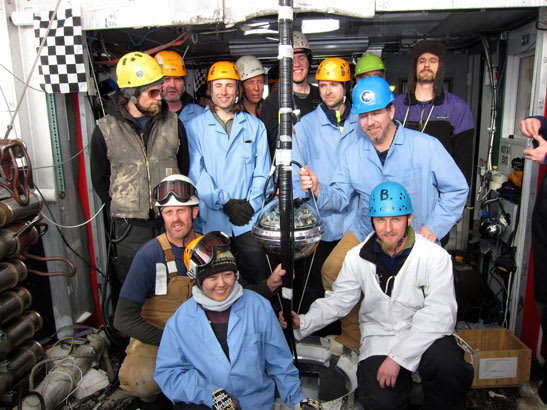 The final deployment team poses with the final DOM in the IceCube array