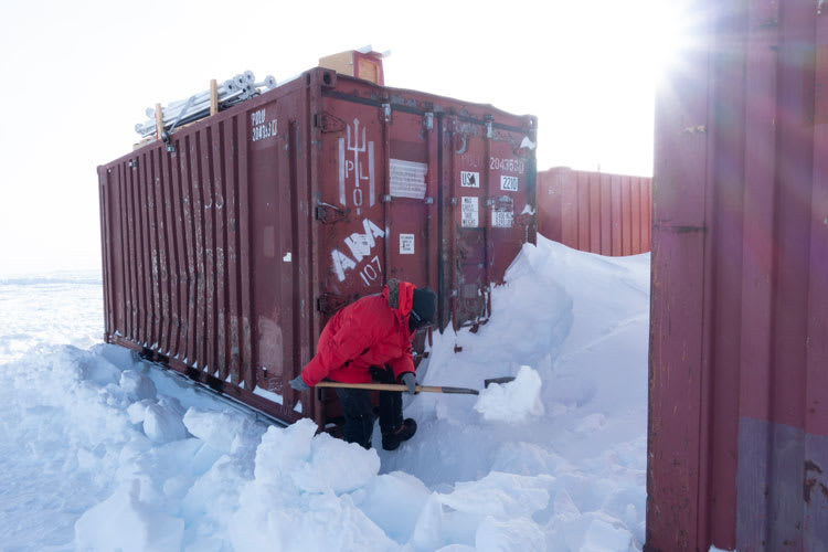 Person in red parka shoveling snow outside the doors of a shipping container.
