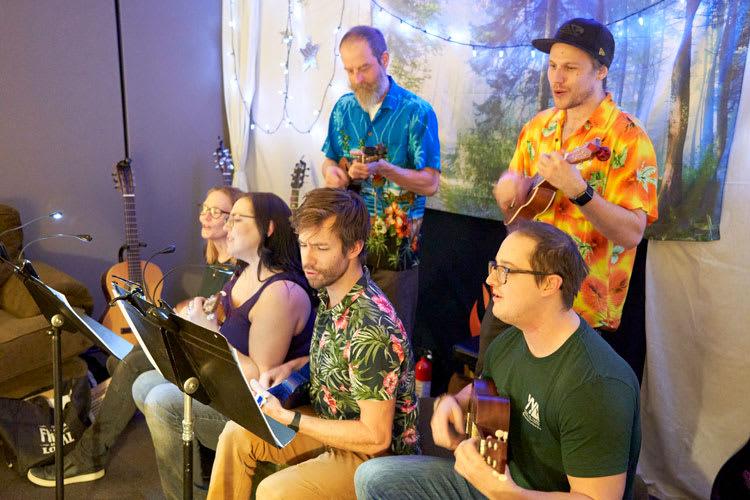 Six people playing ukuleles and singing.