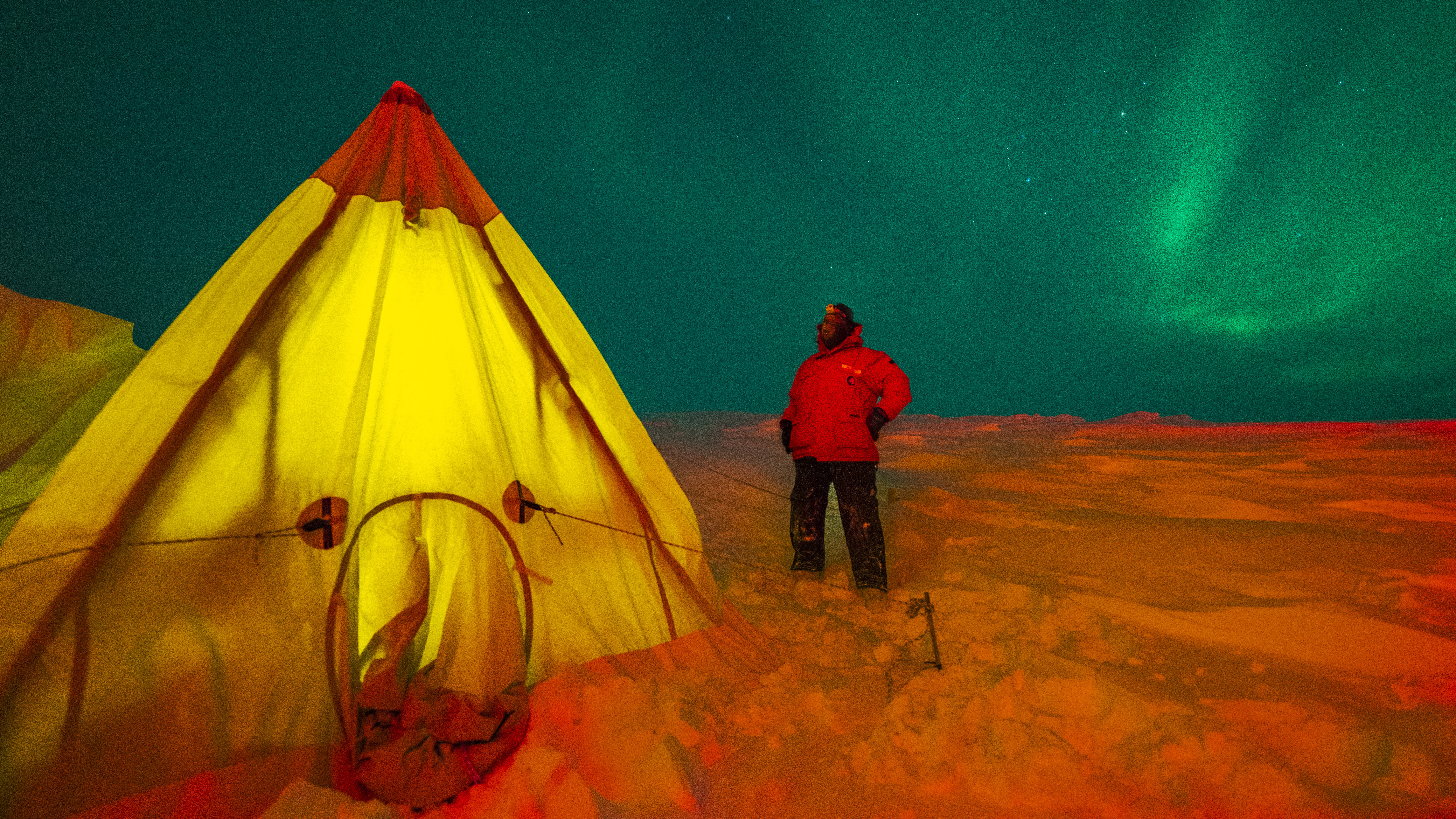 Night shot of person standing outside a pitched tent with green aurora sky.