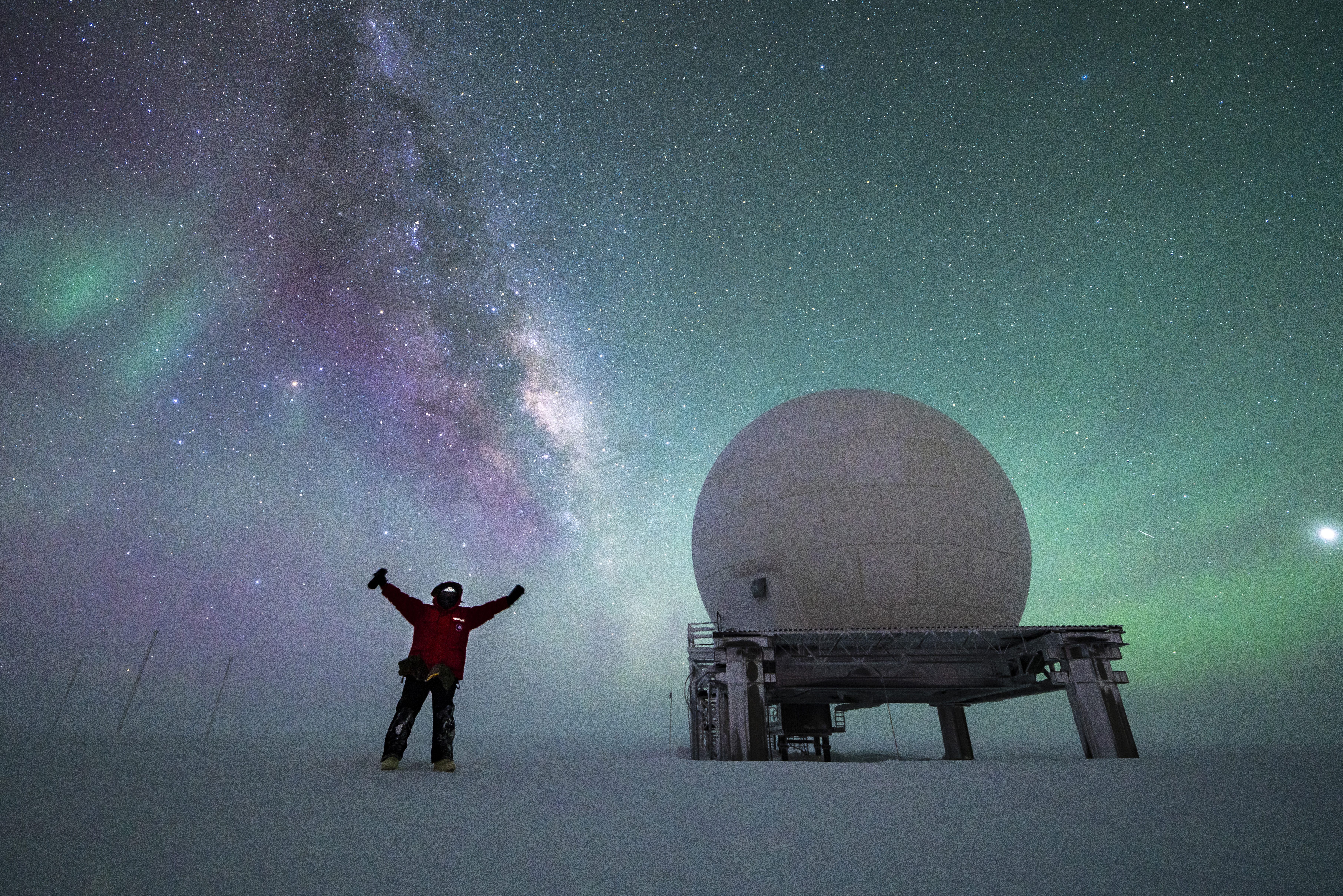 Sky full of auroras and Milky Way, person standing with arms up near a satellite dome.