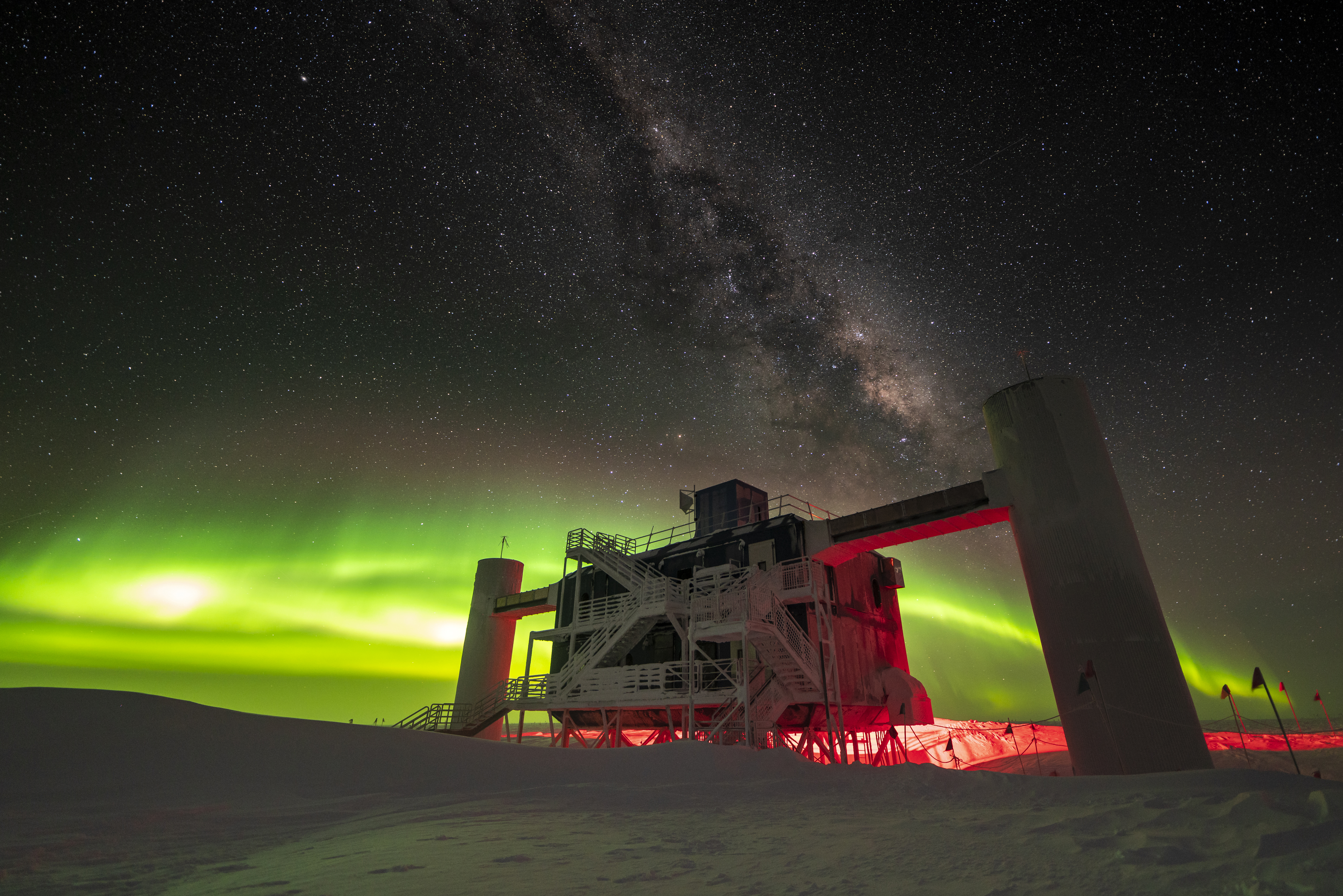 IceCube Lab backlit by low green auroras, with Milky Way overhead.