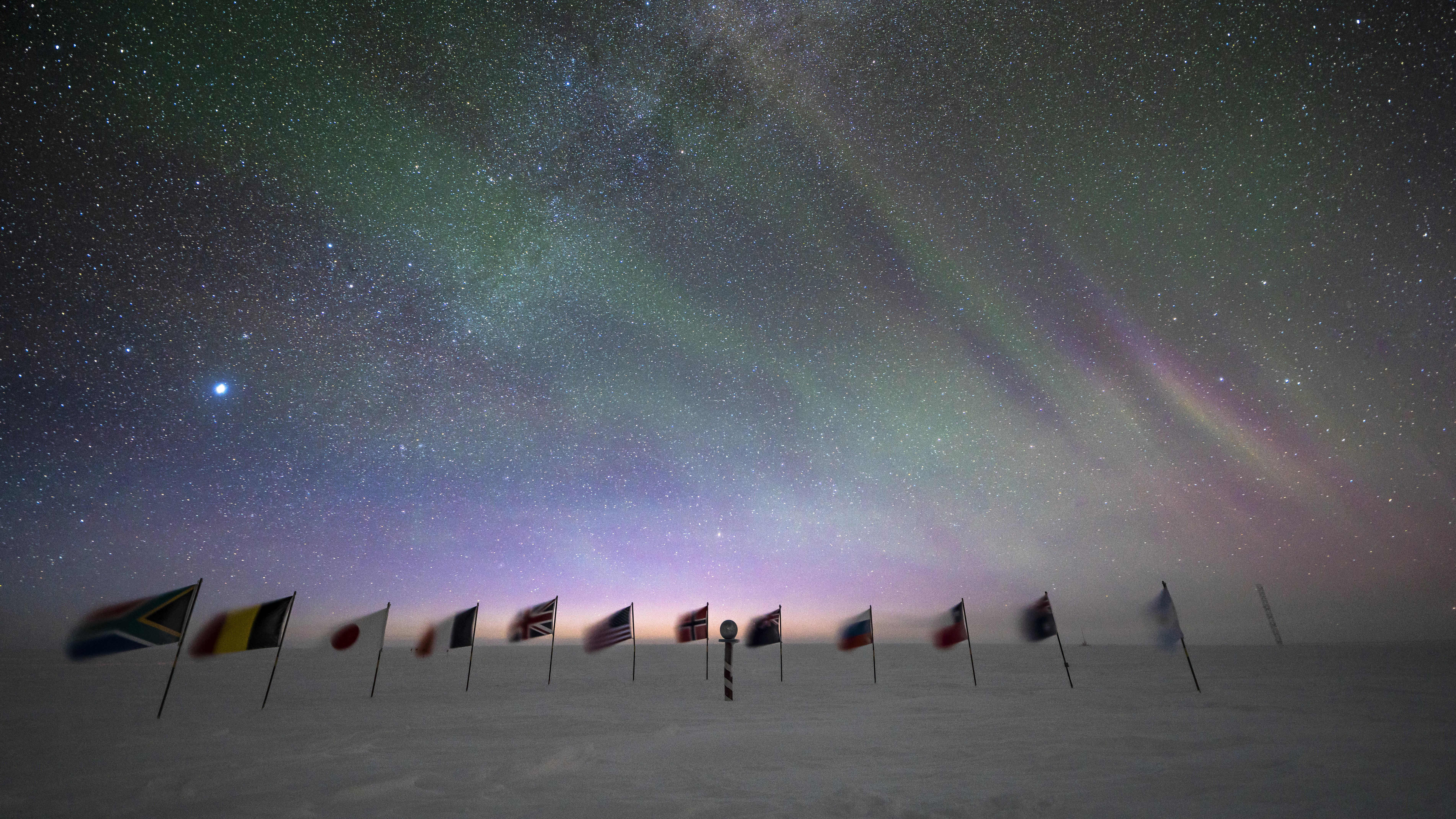 Early sunrise behing the flags at the ceremonial South Pole.