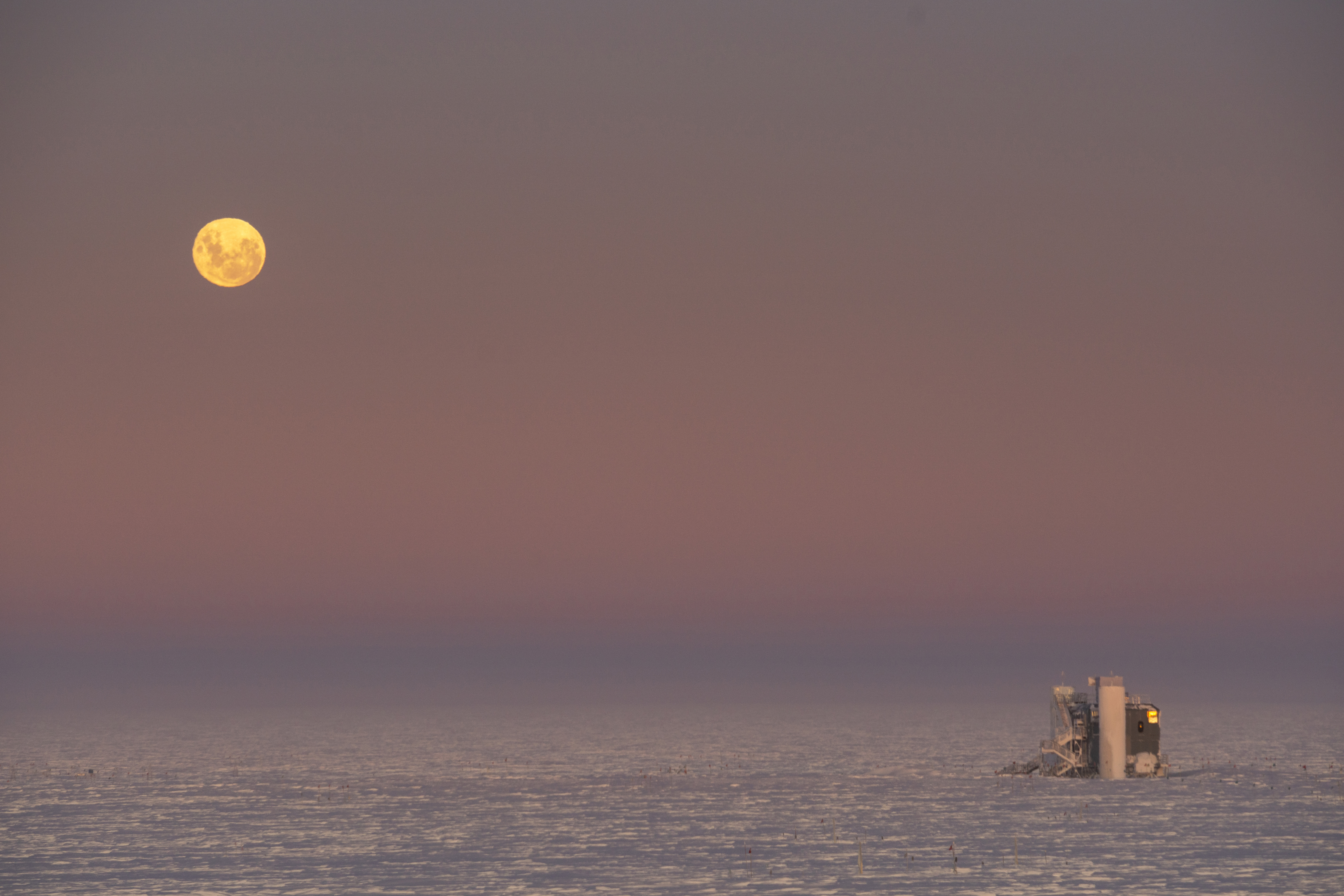 Full moon low in sky above IceCube Lab at sunrise.