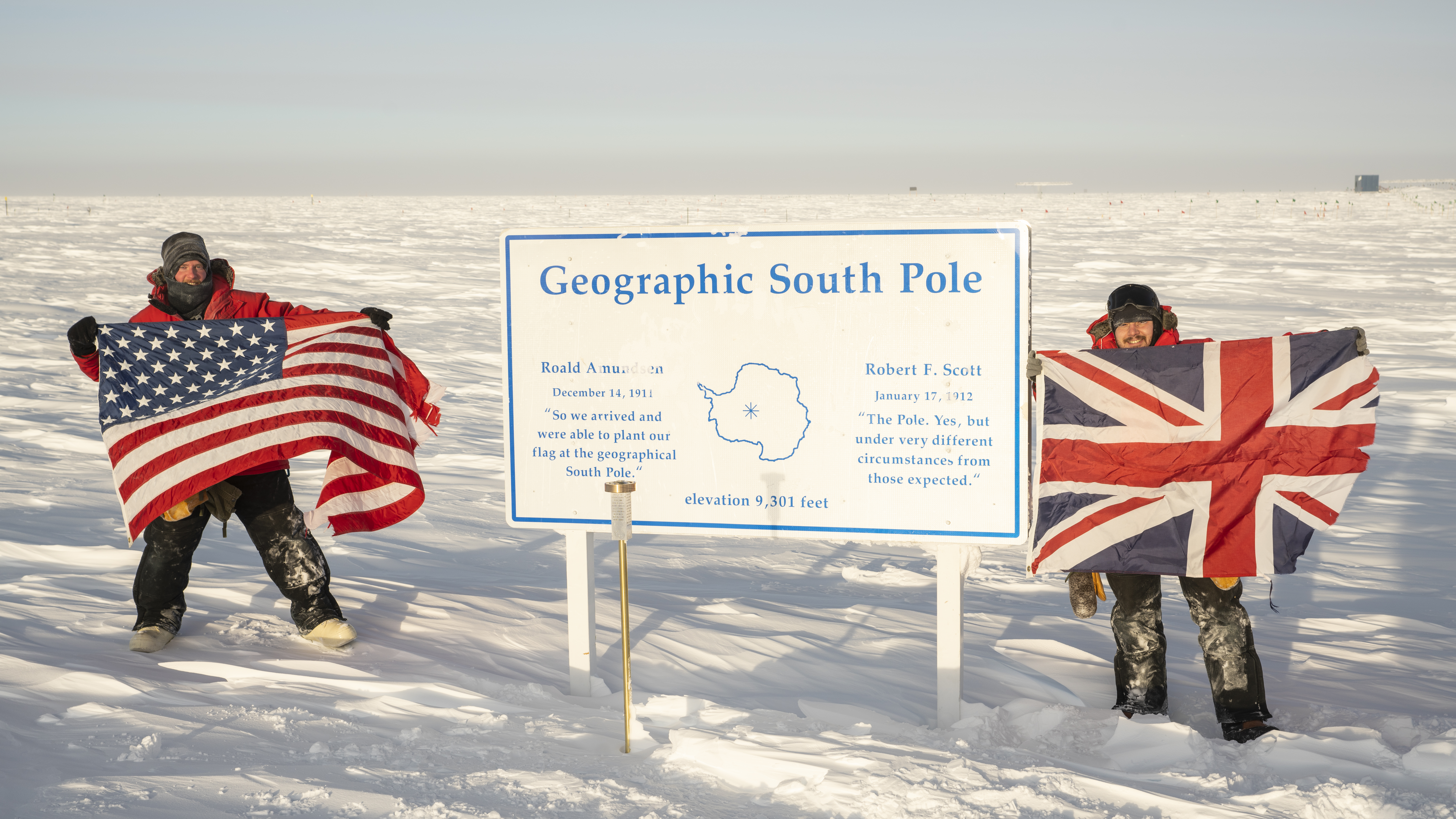 IceCube winterovers holding US and British flags next to geographic South Pole sign.