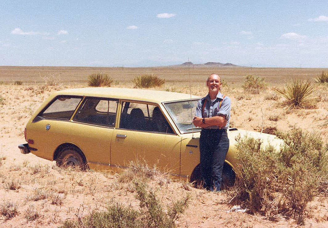 A man wearing rainbow suspenders leaning against a yellow car in a desert landscape.
